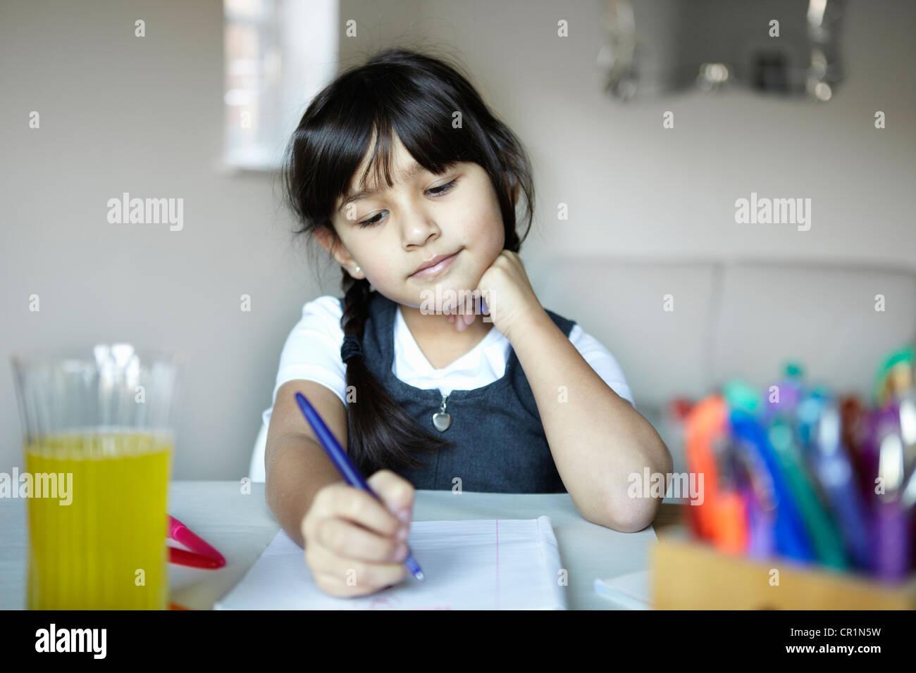 Schulmädchen schreiben am Schreibtisch Stockbild
