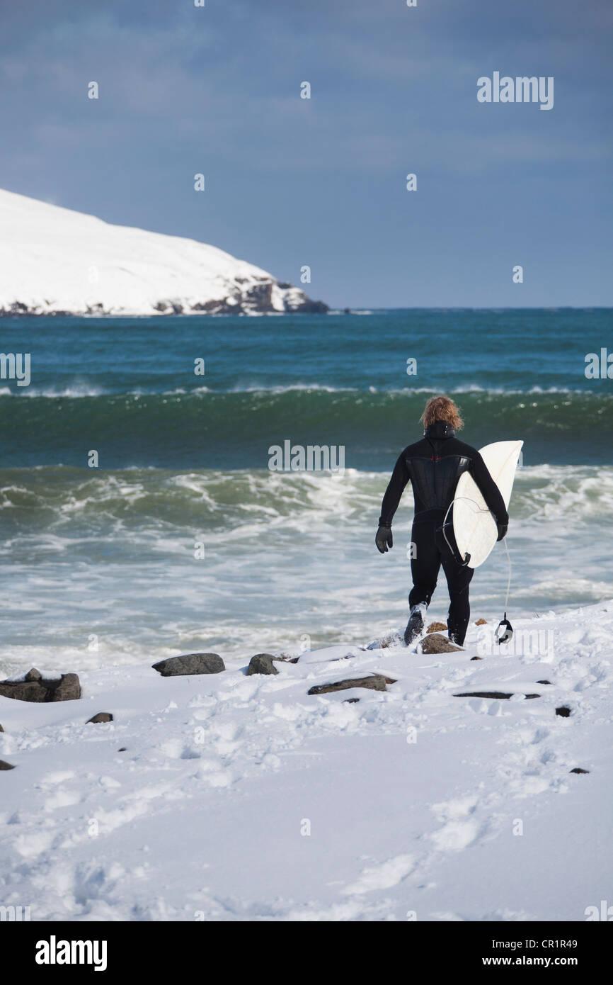 Surfer mit Surfbrett am verschneiten Strand Stockbild