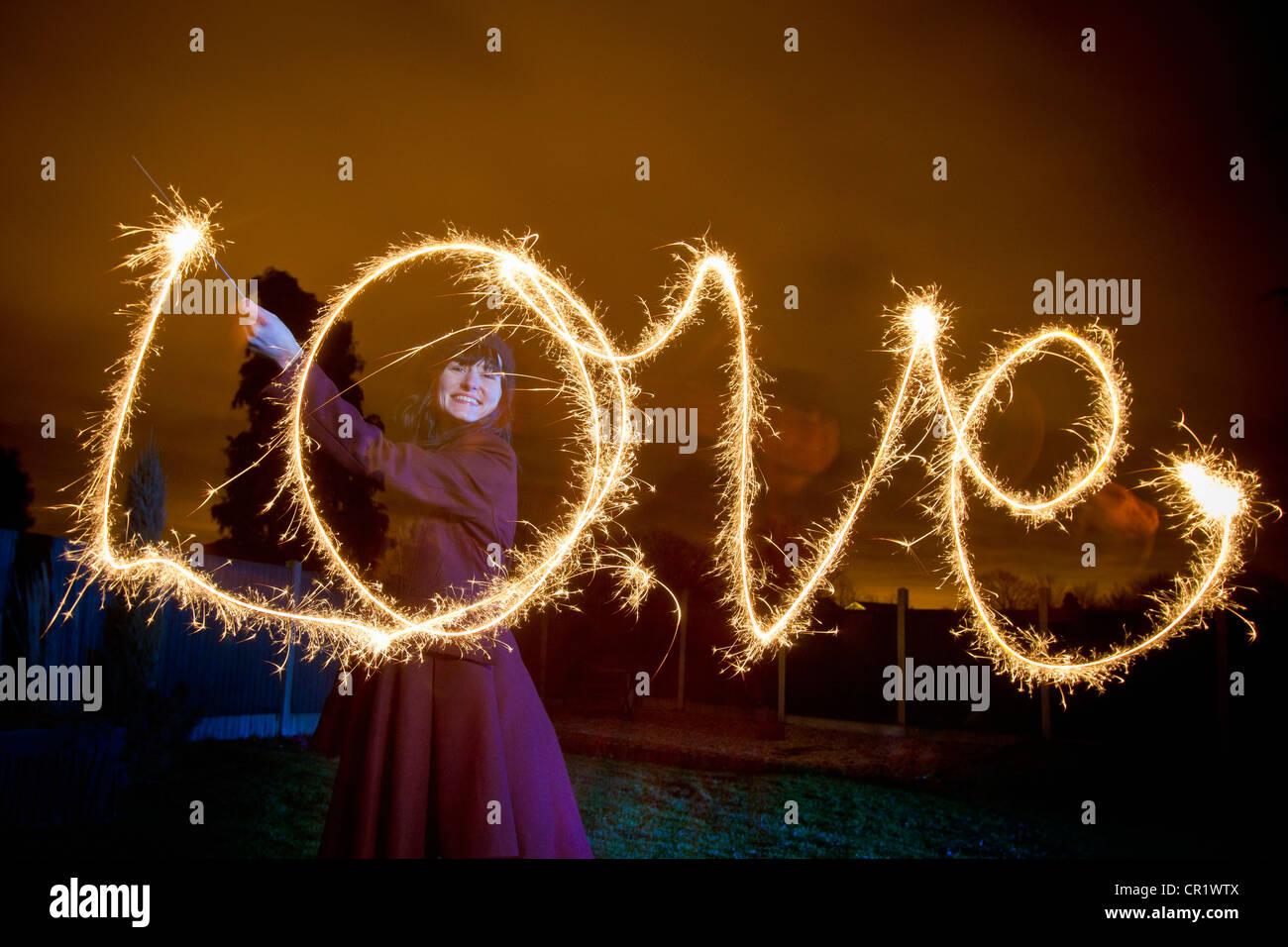 Frau schreiben Liebe mit Wunderkerze Stockbild