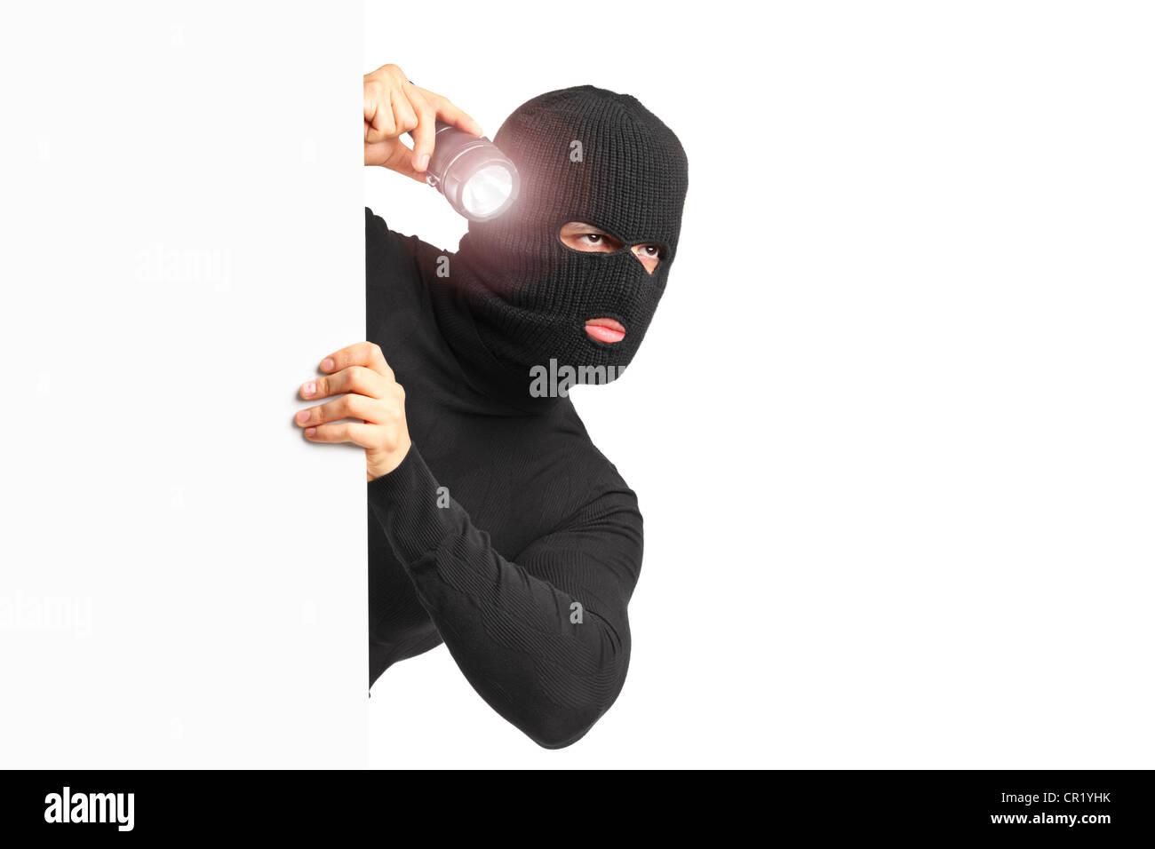 Ein Dieb mit Raub Maske hält eine Taschenlampe hinter einer weißen Blende isoliert auf weißem Hintergrund Stockbild