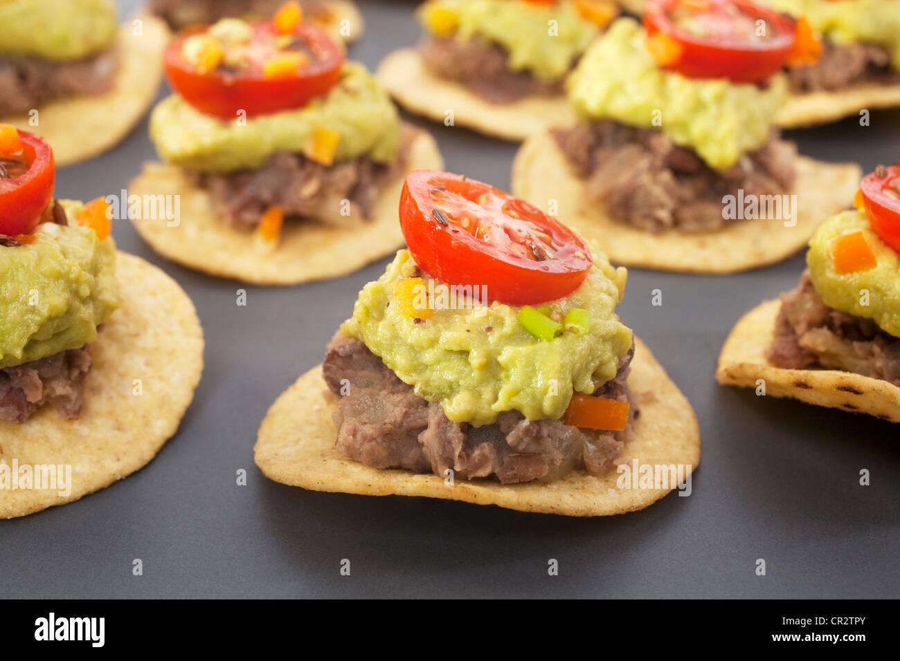 Würzige mexikanische Party Essen, Mais-Chips garniert mit gebackenen Bohnen, Tomaten und Avocado Salsa. Stockbild