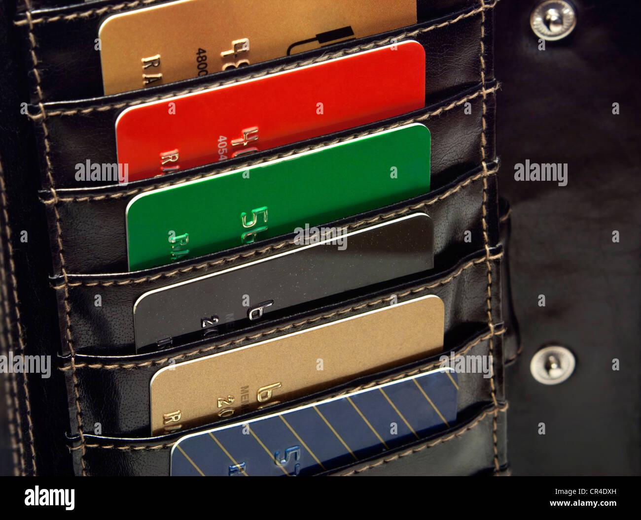Mehrere bunte rot grün schwarz blau gold Kreditkarten in die schwarze Geldbörse. Stockbild