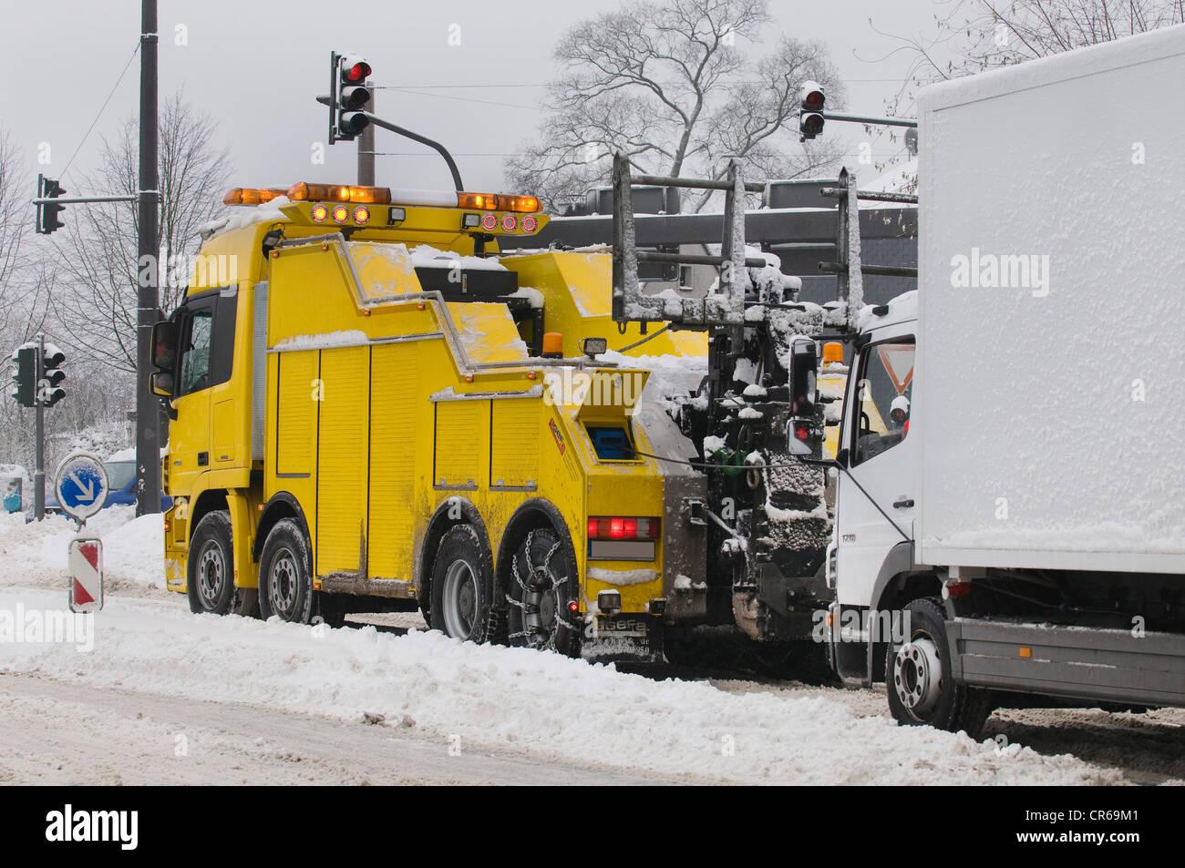 Winter, LKW geschleppt durch einen großen Abschleppwagen auf einer verschneiten Straße Stockbild