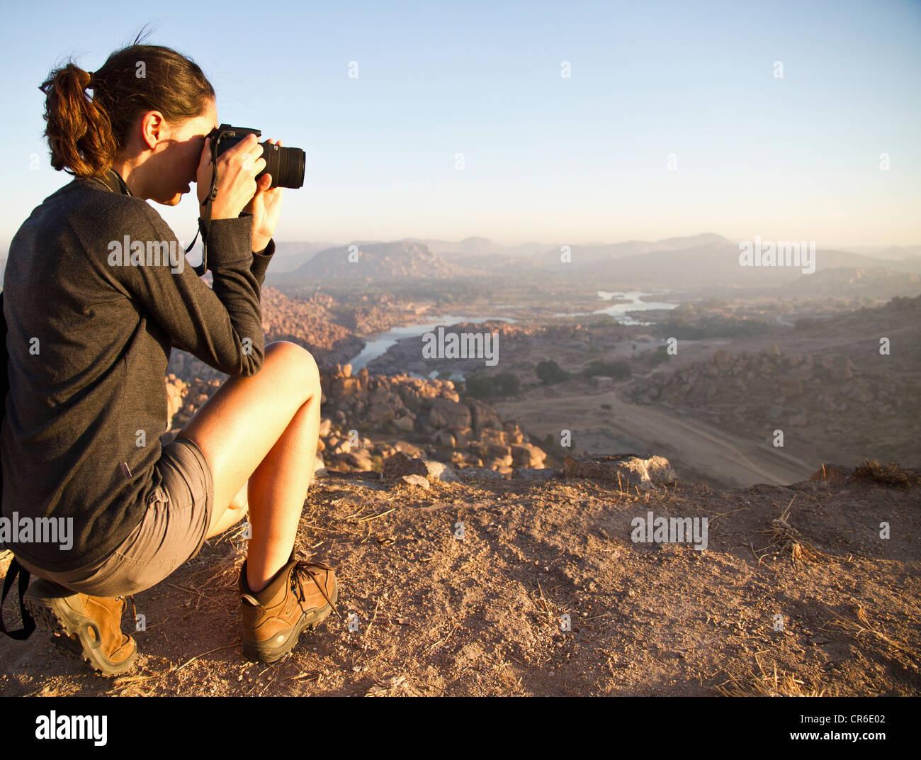 Indien, Karnataka, junge weibliche Touristen fotografieren auf Hügel in Hampi Stockfoto