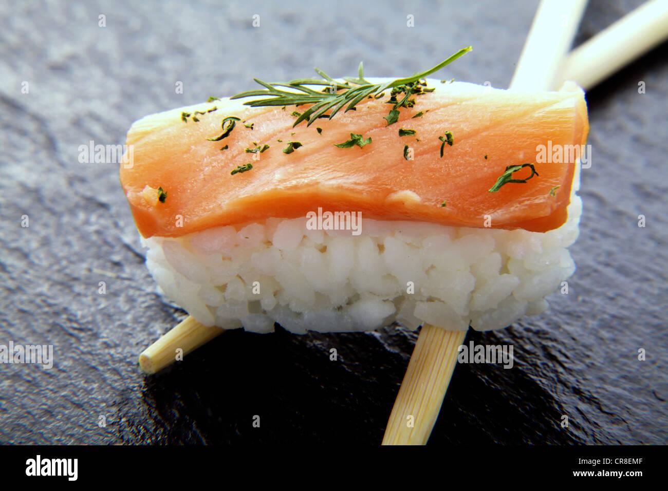 Sushi, Nigiri mit Lachs und Stäbchen auf eine Schieferoberfläche Stockbild
