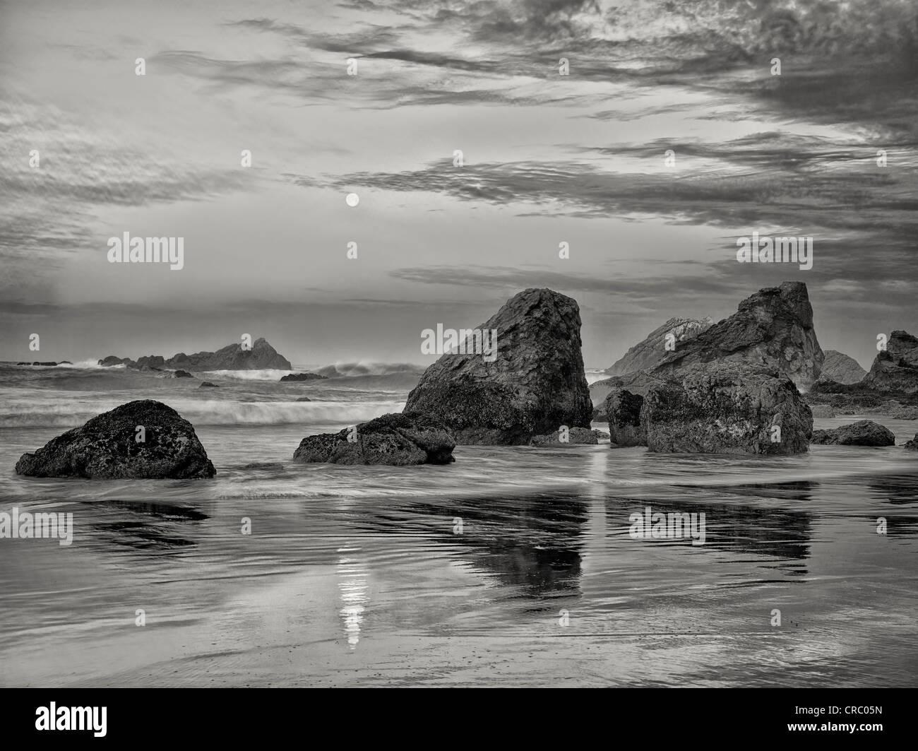 Sonnenaufgang und volle Monduntergang mit Reflexion Harris Beach State Park, Oregon Stockbild