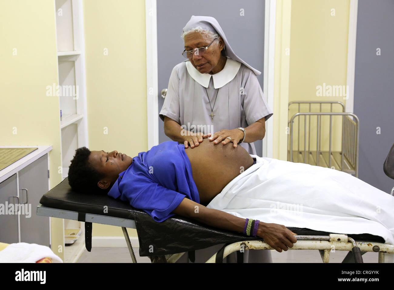 Katholischen Schwester und ausgebildete Hebamme untersucht hochschwangere Frau Patienten in der Entbindungsstation Stockbild