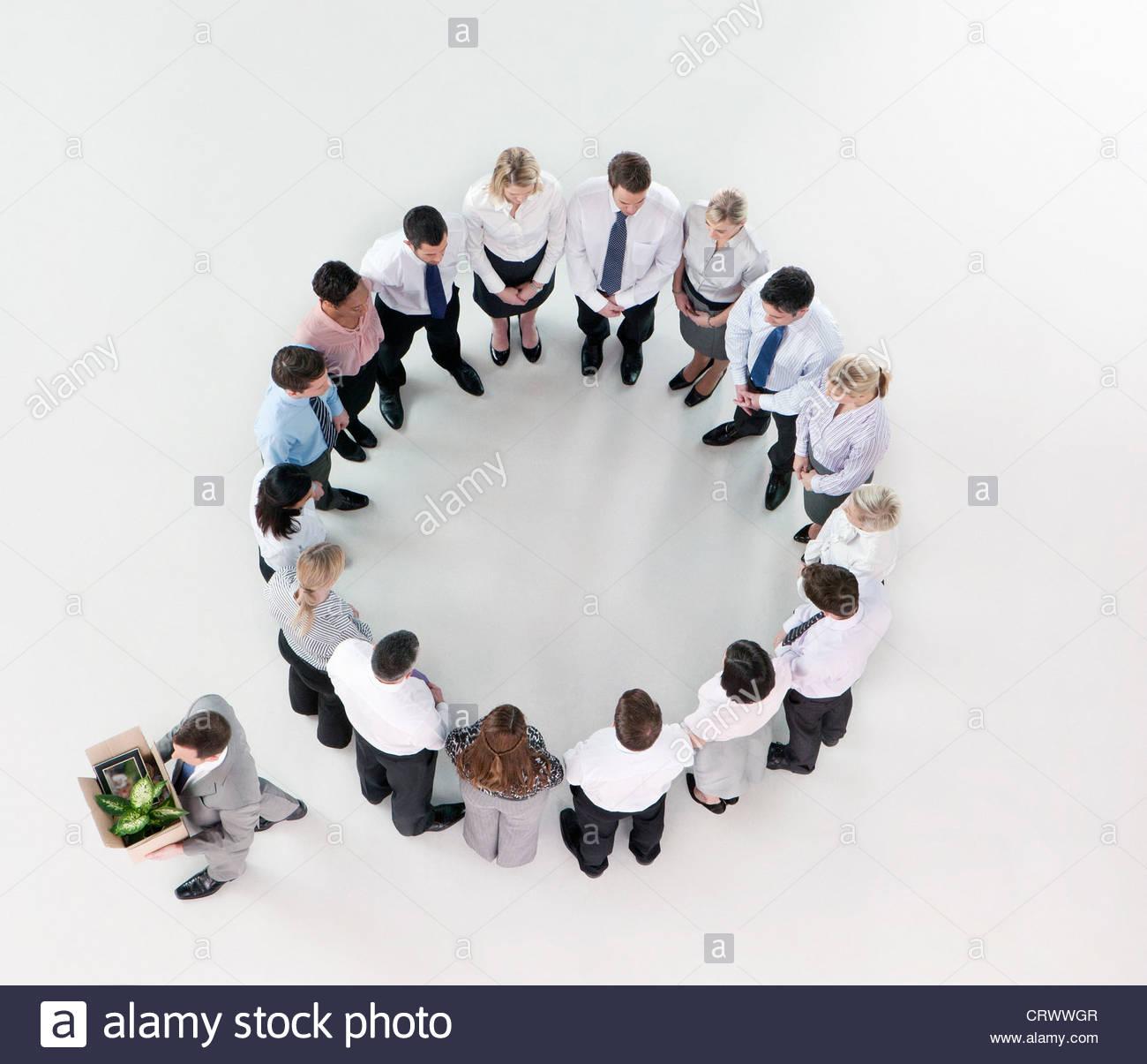 Geschäftsmann mit Box von hab und gut zu Fuß entfernt von Geschäftsleuten Kreis bilden Stockbild
