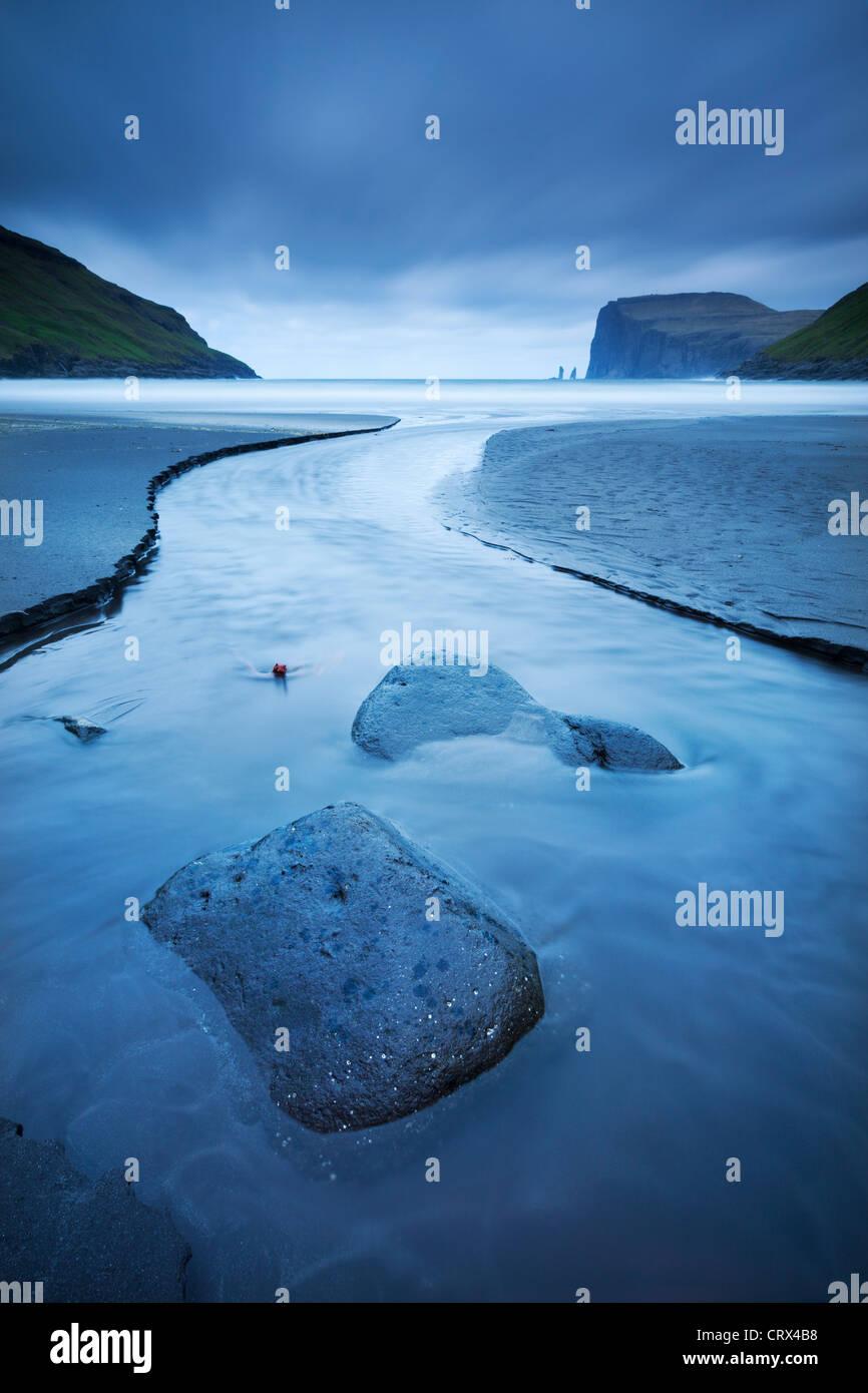 Ein Stream läuft ins Meer bei Tjornuvik auf der Insel Streymoy auf den Färöer Inseln. (Juni) Frühjahr Stockbild
