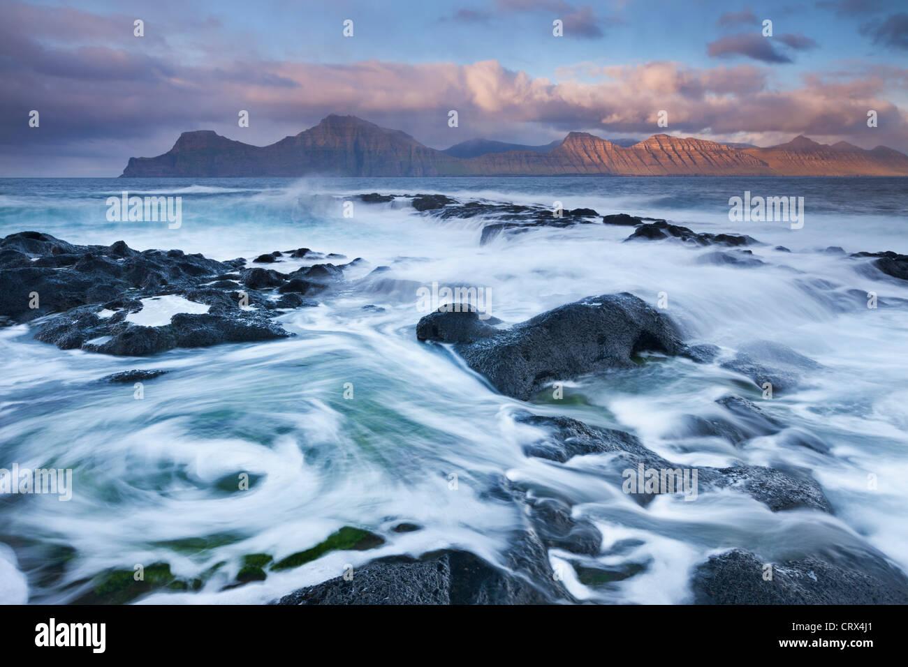 Wogende Wellen brechen über den felsigen Ufern an Gjogv auf der Insel Eysturoy, Färöer. (Juni) Frühjahr Stockbild