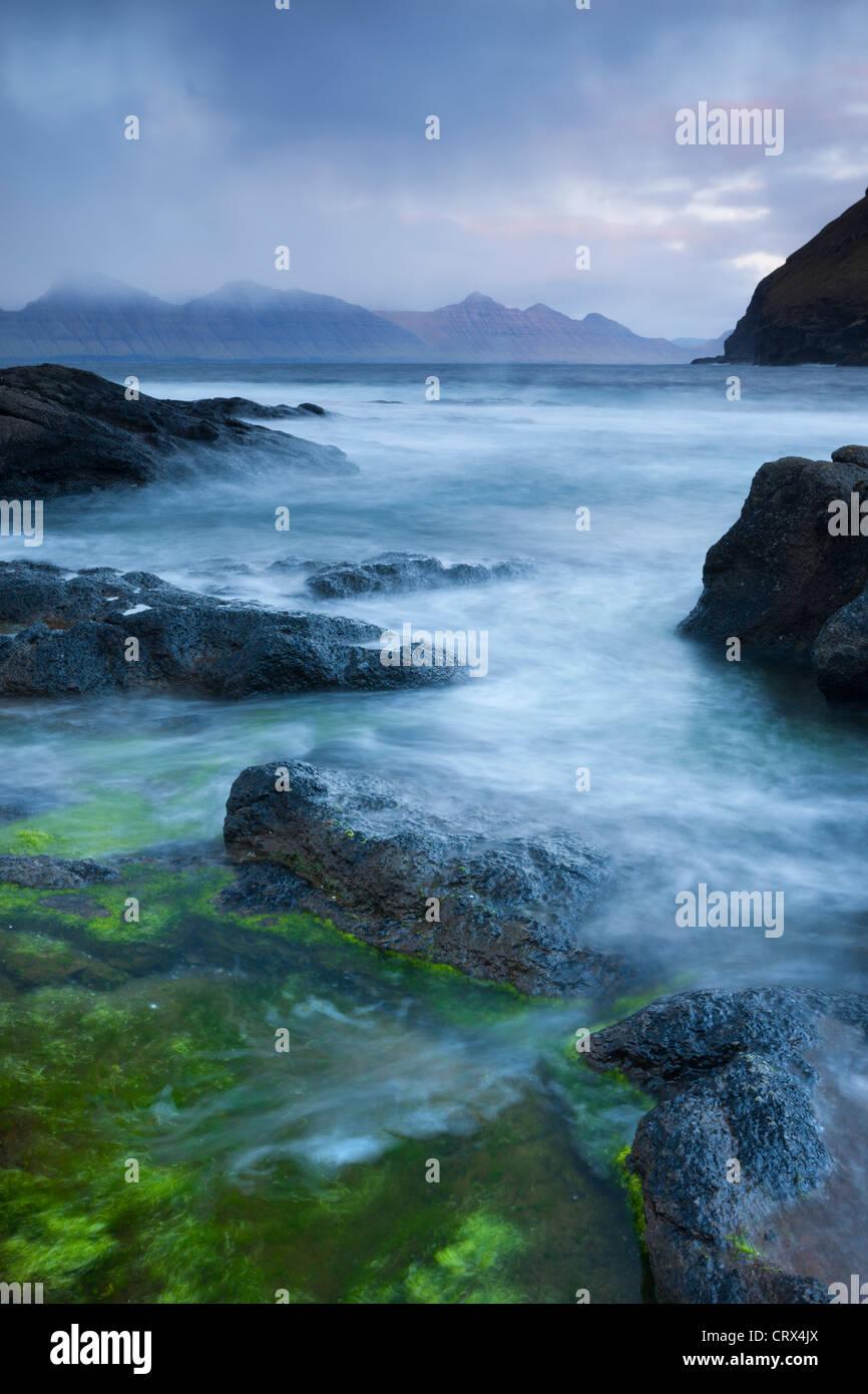 Mit Blick auf die Insel Kalsoy von den felsigen Ufern des Gjogv, Eysturoy, Färöer-Inseln. (Juni) Frühjahr Stockbild