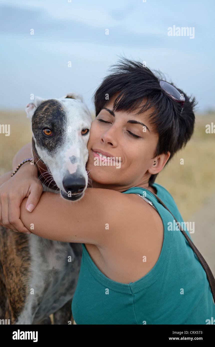Attraktive Frau posiert mit ihren spanischen Windhund in der Natur Stockbild