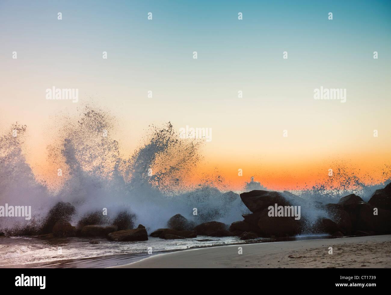 Wellen an der felsigen Strand bei Sonnenuntergang Stockbild