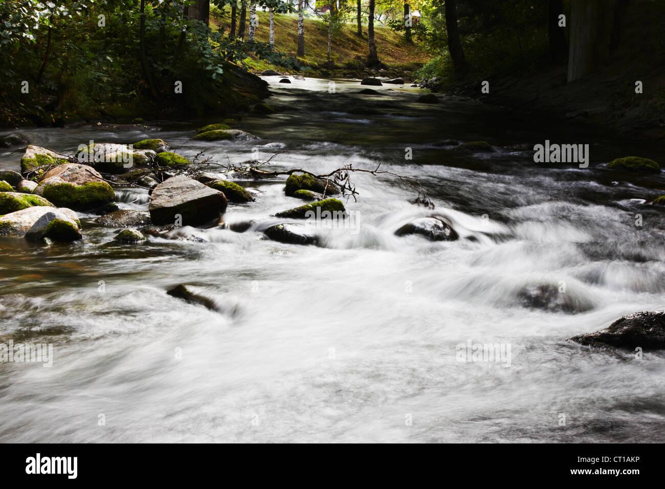 Verschwommene Sicht auf Fluss Rauschen über Felsen Stockbild