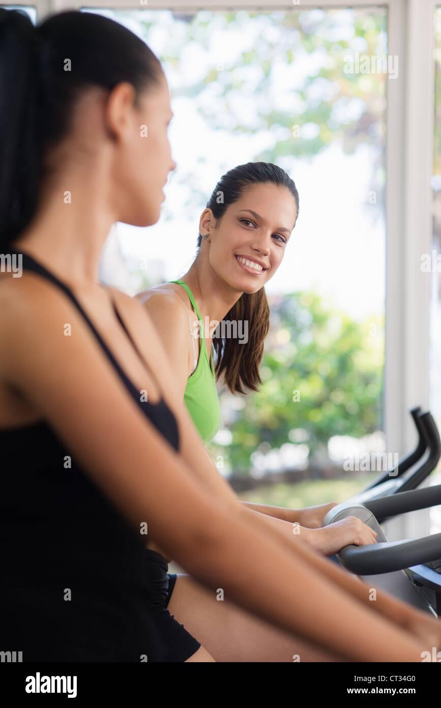 Junge Frauen reden und lachen während der Arbeit am Heimtrainer im Wellnessclub Stockbild