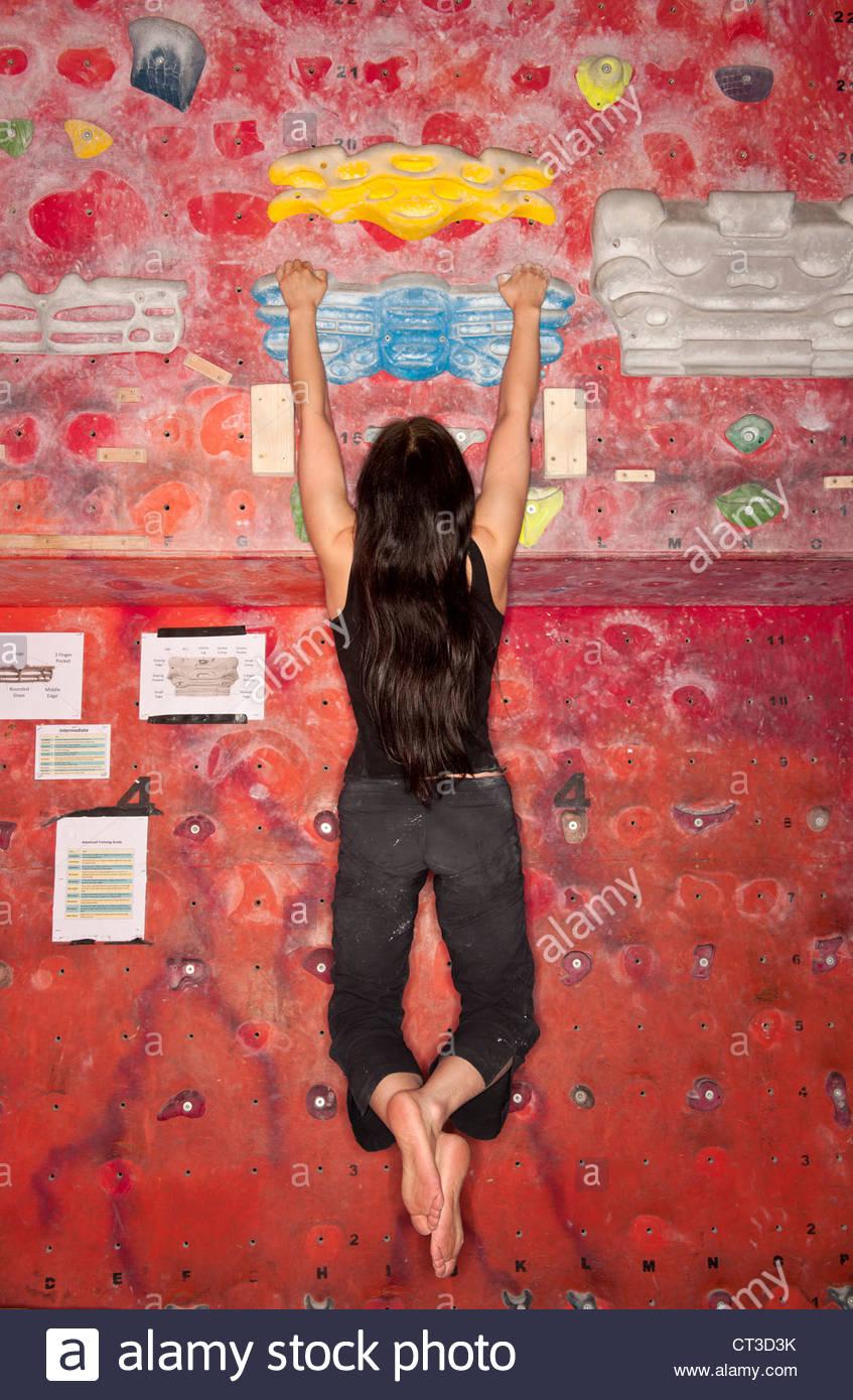 Kletterer an indoor Felswand aufgehängt Stockbild