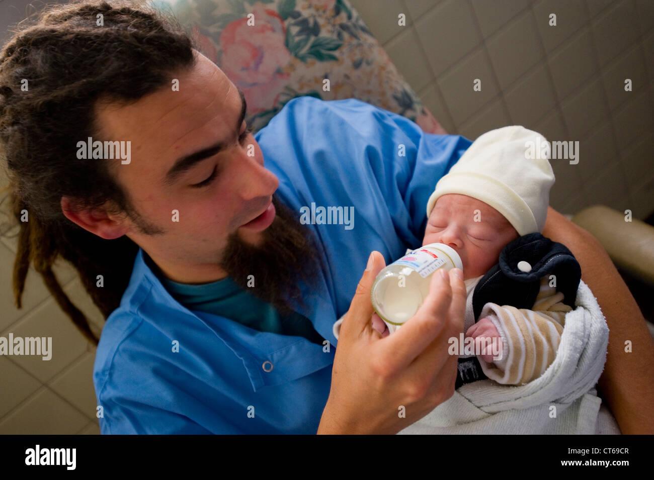 NEUGEBORENE MIT BABY-FLASCHE Stockbild