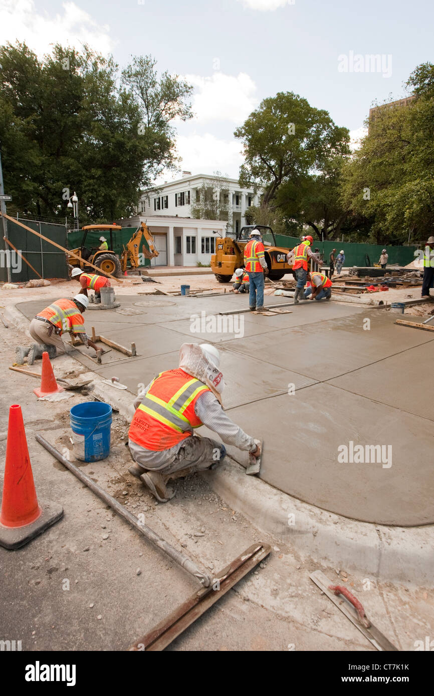 Hispanische männlichen Betonbauer komplette konkrete Bürgersteig vor der neu renovierten Texas des Gouverneurs Stockbild