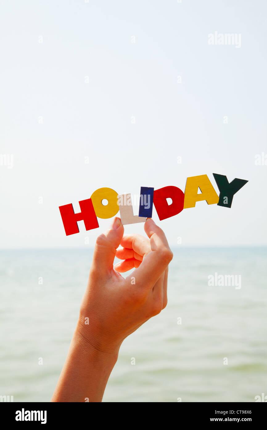 """Weiblichen Hand mit bunten Wort """"Urlaub"""" gegen See bei Tageslicht Stockbild"""