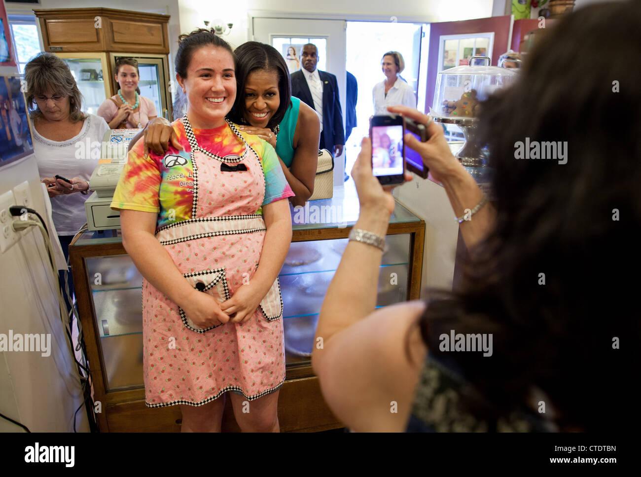 US-First Lady Michelle Obama stellt mit einem Mitarbeiter während eines Besuchs in Mamas Apfelkuchen Co 7. Stockbild