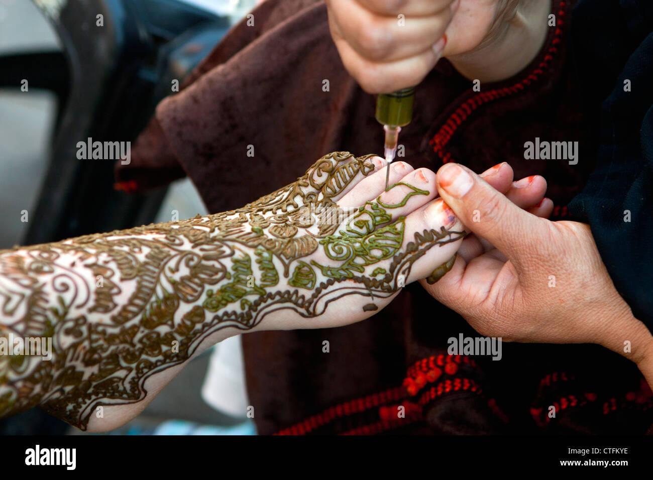 marokko genannt marrakesch platz djemaa el fna frau macht henna tattoo am bein und fu der. Black Bedroom Furniture Sets. Home Design Ideas