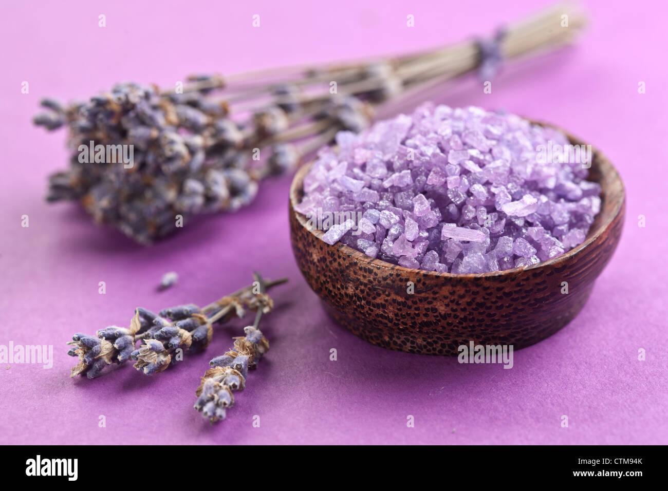 Meersalz und getrocknetem Lavendel auf violettem Hintergrund. Stockbild