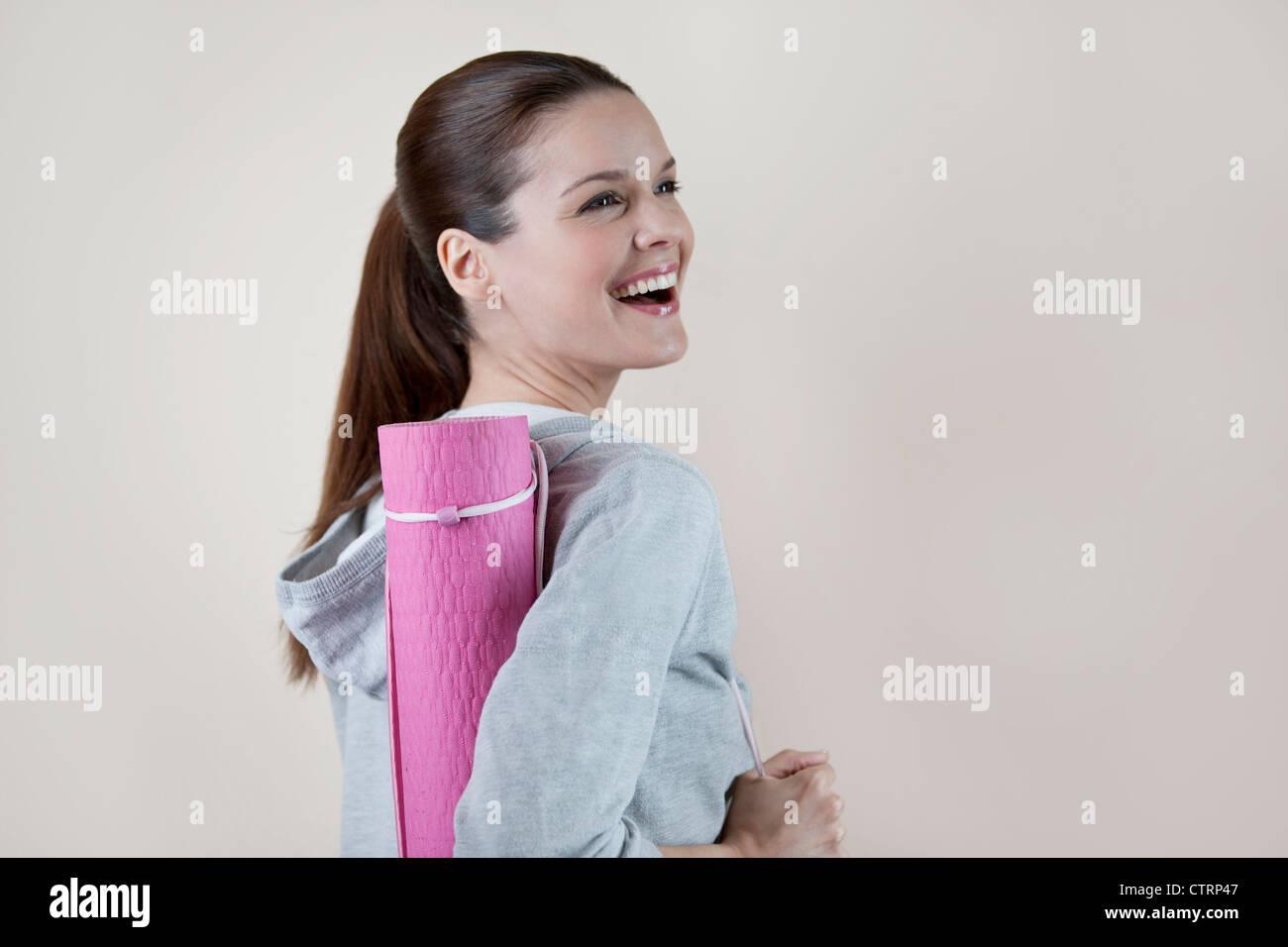 Eine junge Frau trägt eine Yoga-Matte, lachen Stockbild