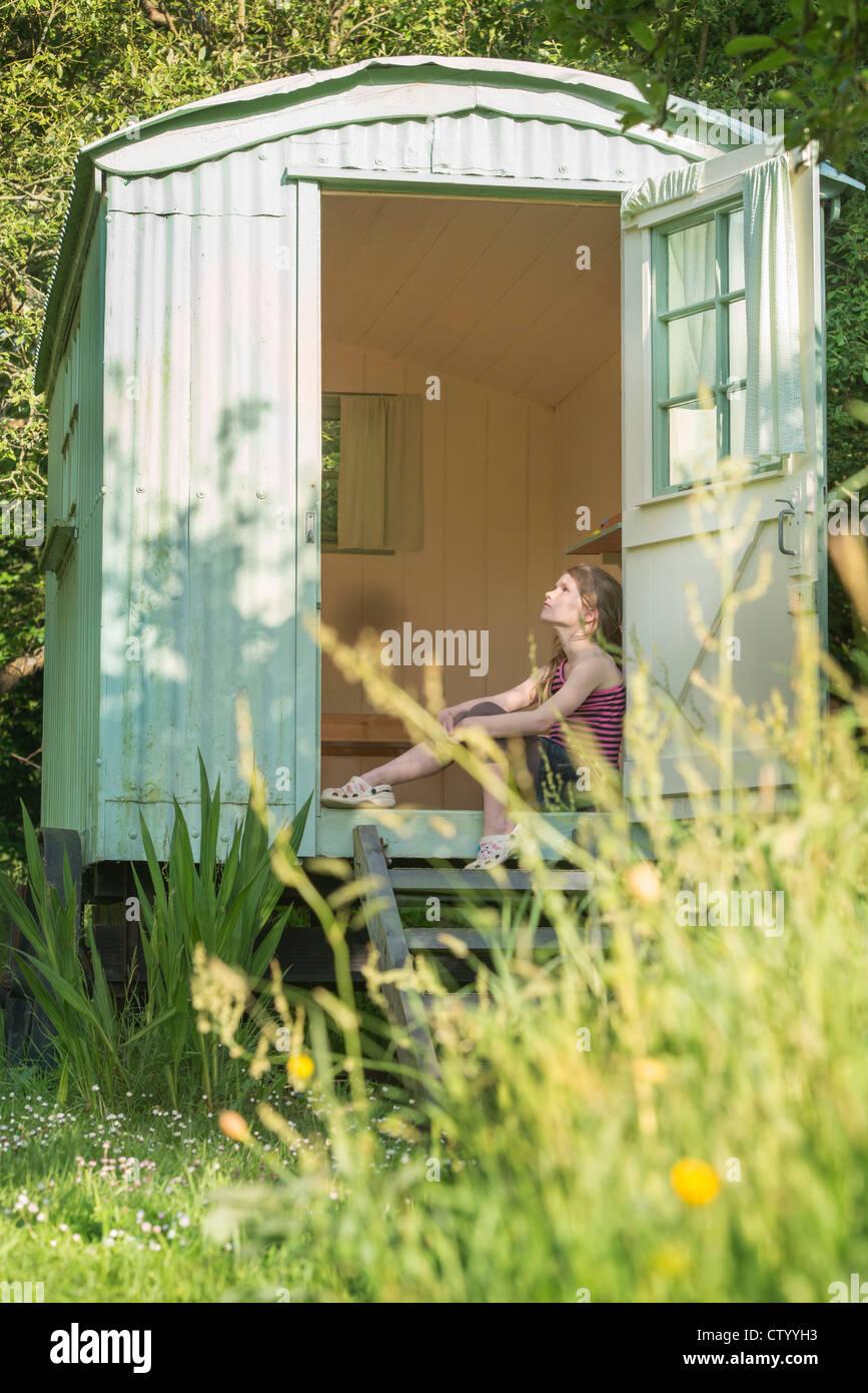 Mädchen sitzen in Tür Stockbild