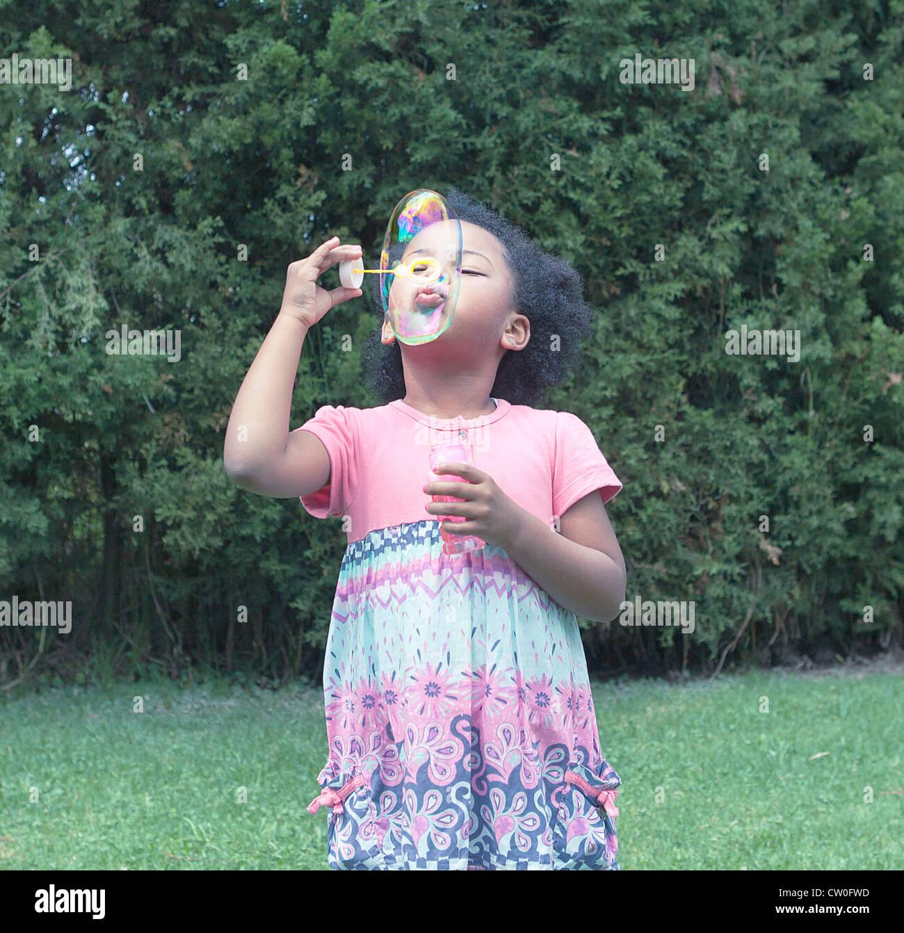 Mädchen bläst Luftblasen im freien Stockbild
