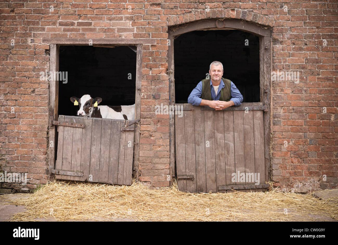 Bauer am Tor der Scheune stehen Stockbild