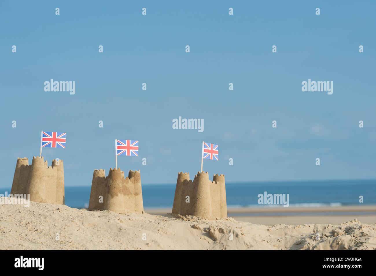 Union Jack-Flaggen in Sandburgen auf einer Sanddüne. Brunnen neben das Meer. Norfolk, England Stockbild