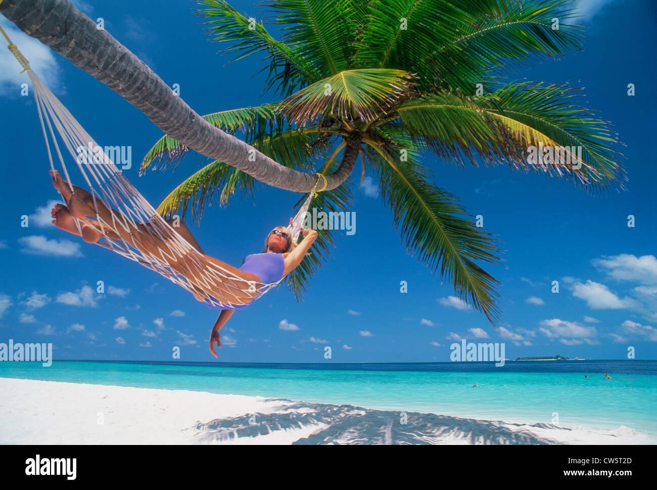 Frau in Hängematte unter Palmen inmitten der idyllischen Urlaub Stockfoto