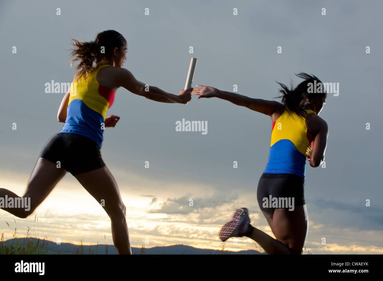 Weibliche Staffel Rennfahrer Staffelstab übergeben Stockbild