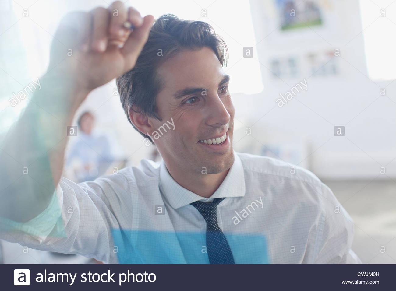 Lächelnde Geschäftsmann gelehnt Glas im Büro Stockfoto
