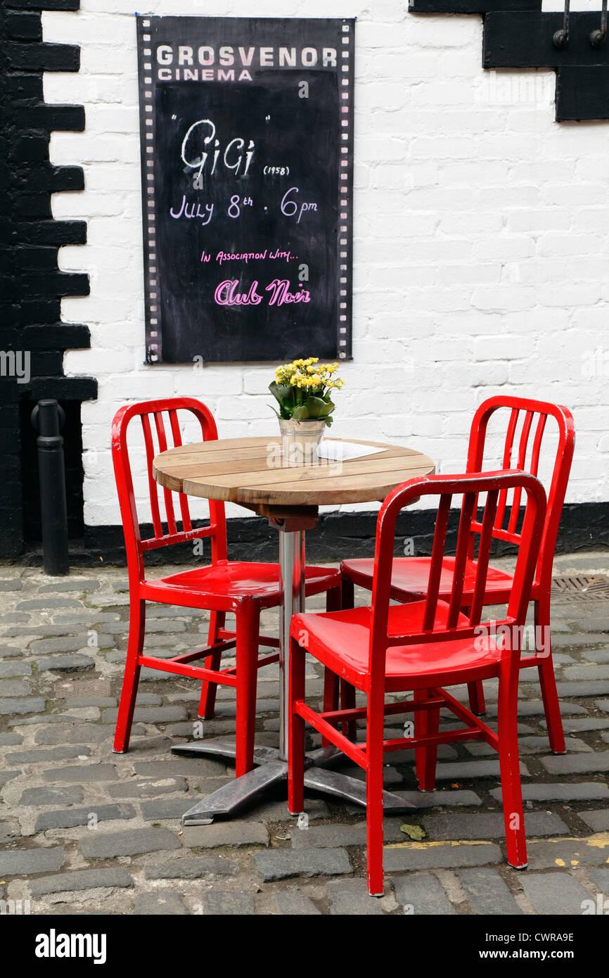 3 rote Stühle um einen Tisch mit Blumen vor der Grosvenor Kino auf Ashton Lane im West End von Glasgow, Scotland, Stockbild