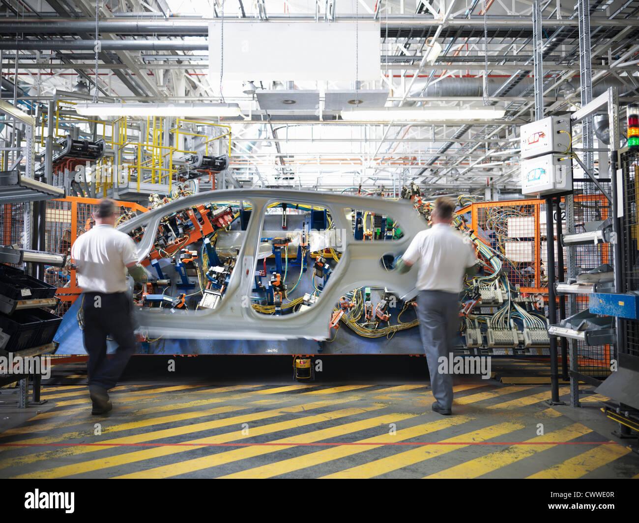 Arbeitnehmer mit Auto Körperteil beim Schweißen jig in Automobilfabrik Stockbild