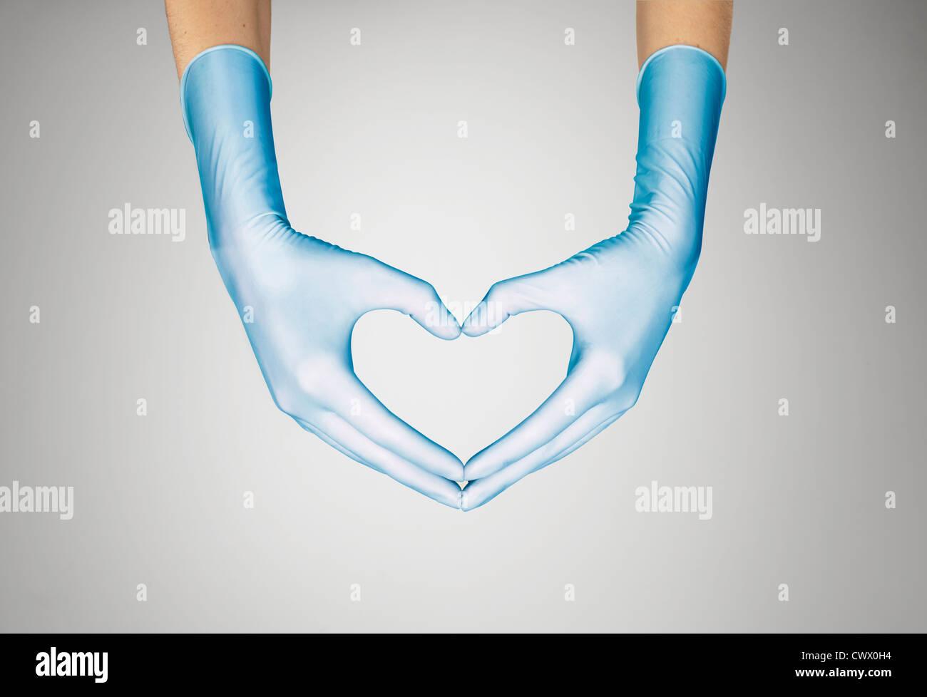Behandschuhten Händen machen Herzform Stockfoto