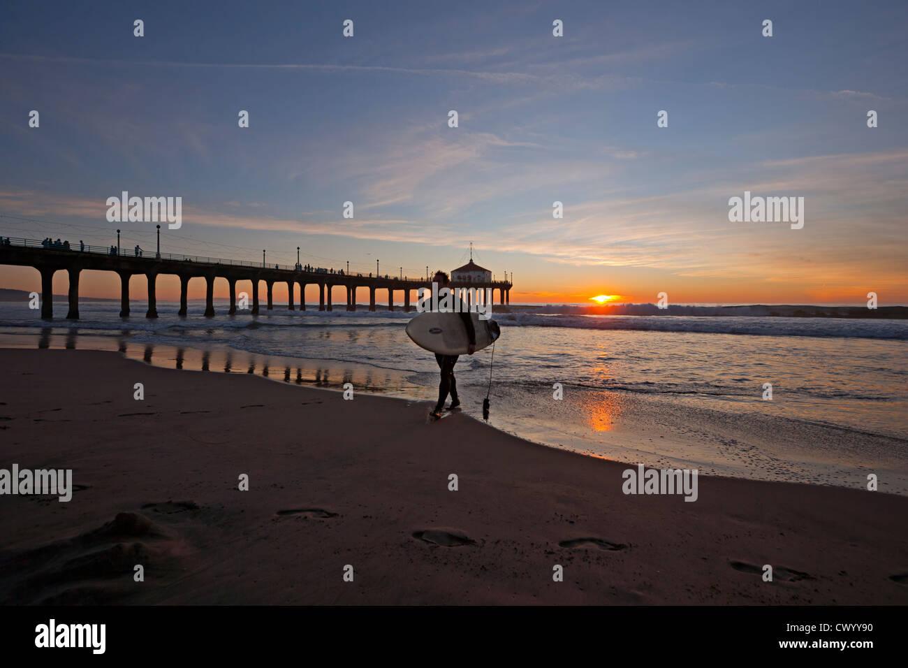 Surfer verlässt das Meer den Pier und den Sonnenuntergang in Manhattan Beach, Kalifornien, USA Stockbild