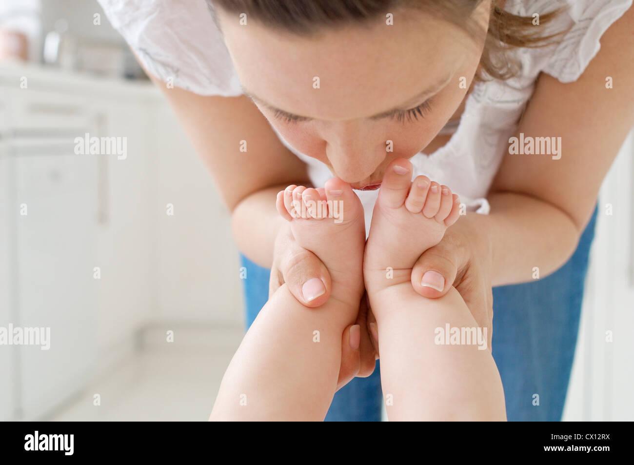 Mutter des Babys küssen Füße Stockbild