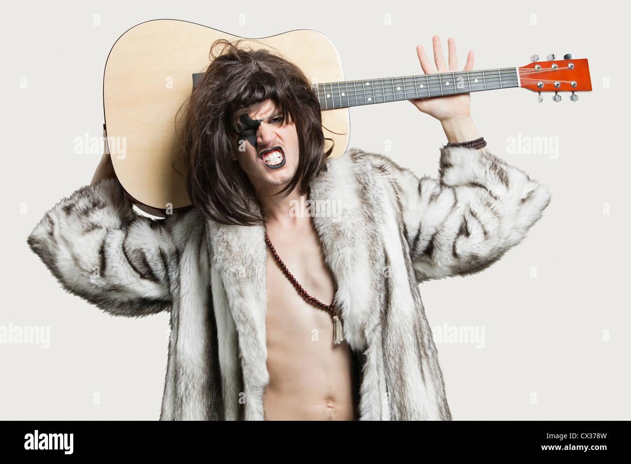 Porträt des jungen männlichen Musiker mit Gitarre ballte Zähne auf grauem Hintergrund Stockbild