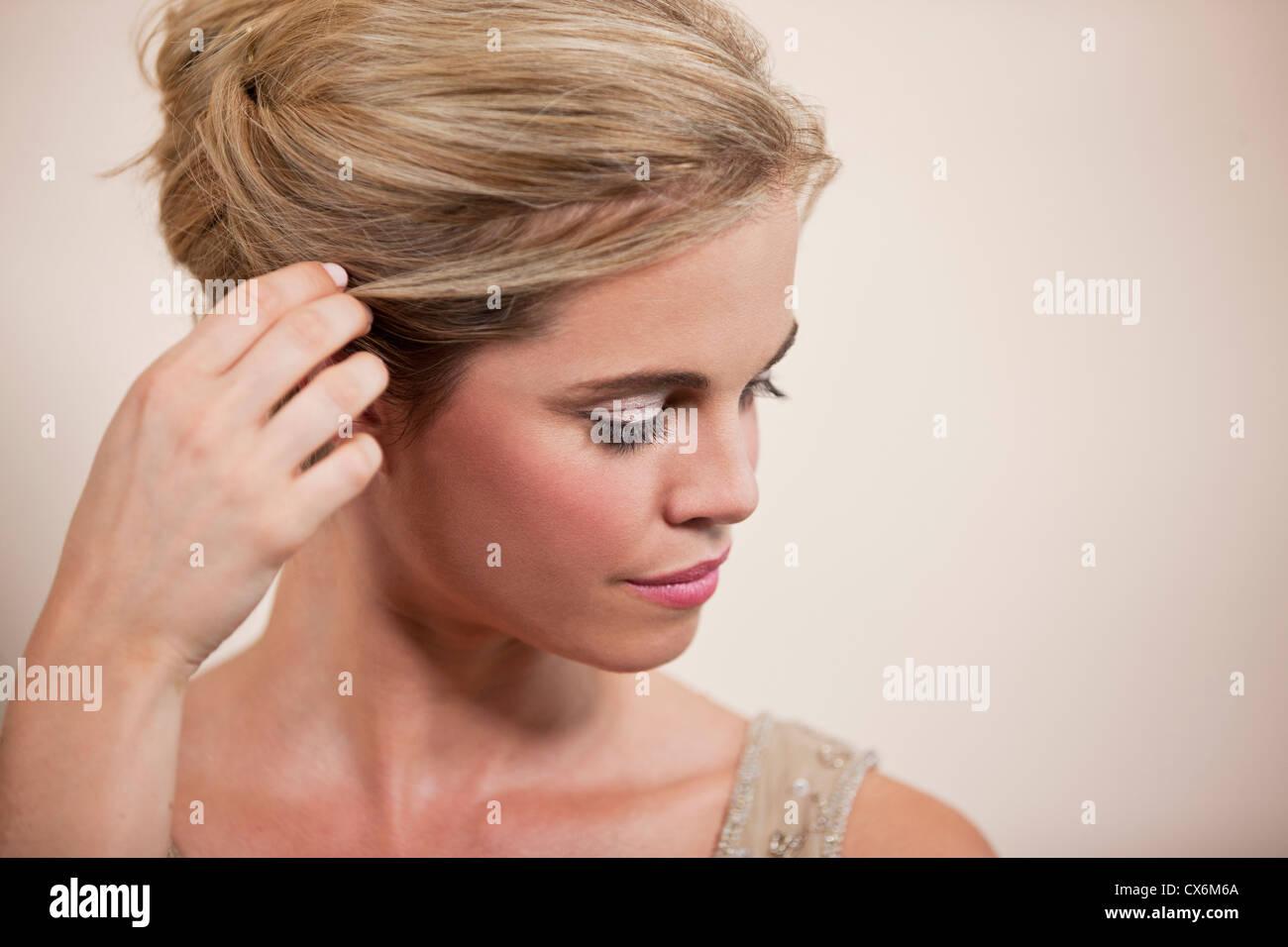 Eine junge Frau ihr Haar hinter ihr Ohr stopfte Stockbild