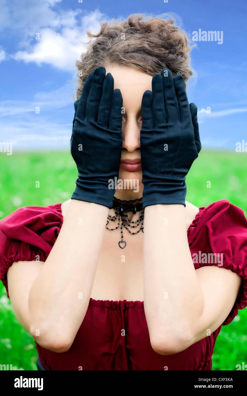 eine Frau mit einem roten Periode Kleid verbirgt ihr Gesicht mit den Händen in schwarzen Handschuhen Stockbild