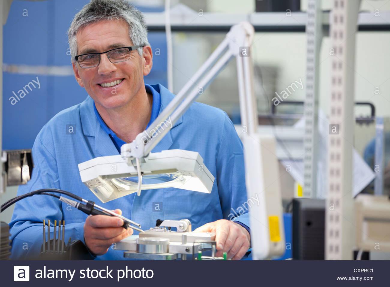 Porträt von lächelnden Techniker arbeiten am Fließband in Hi-Tech-Gerätewerk Stockbild
