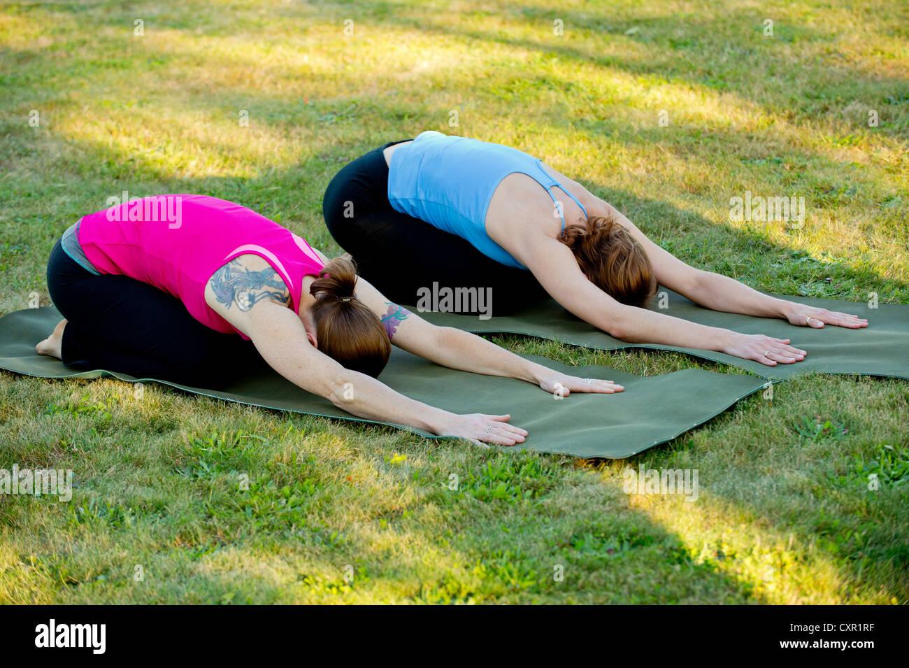 Zwei Frauen erstreckt sich auf Yoga-Matten im freien Stockbild