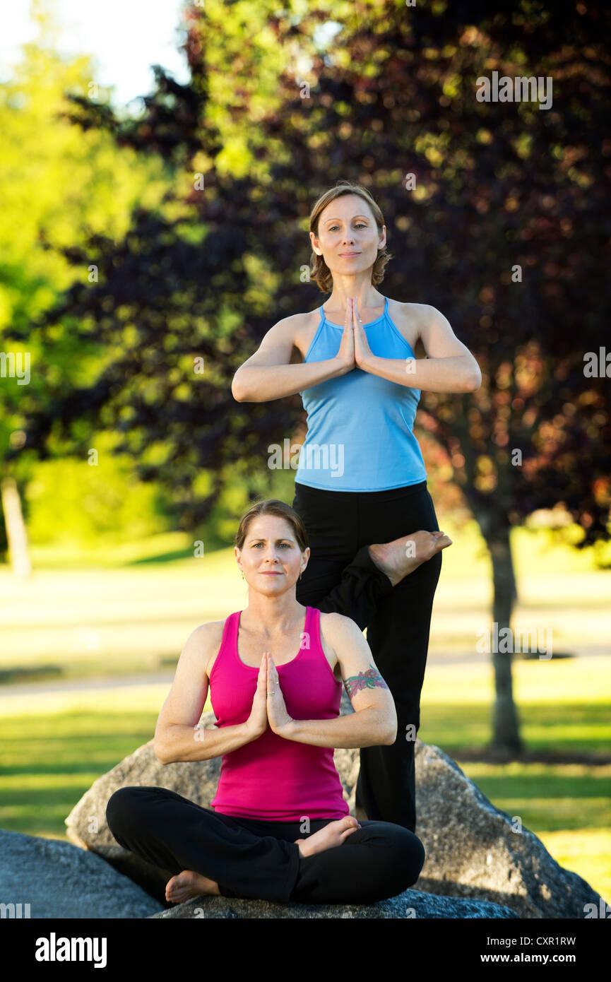 Zwei Frauen in Yoga-Posen auf Felsen Stockbild