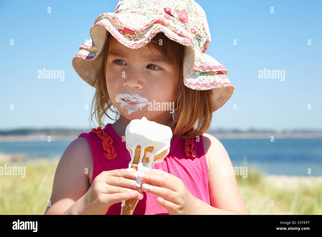 Mädchen, Essen ein Eis am Strand Stockbild