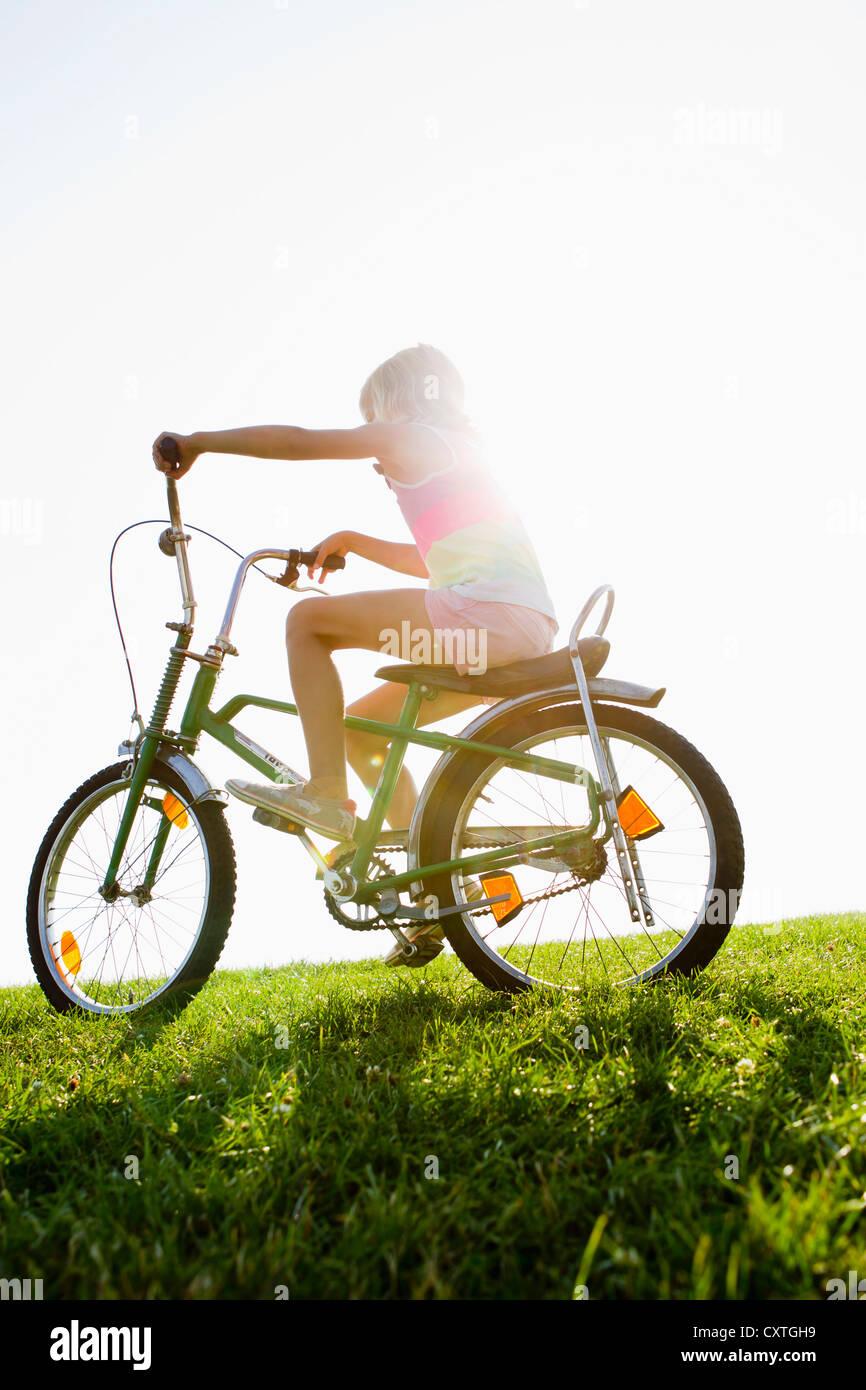 Mädchen Reiten Fahrrad in Rasen Stockbild