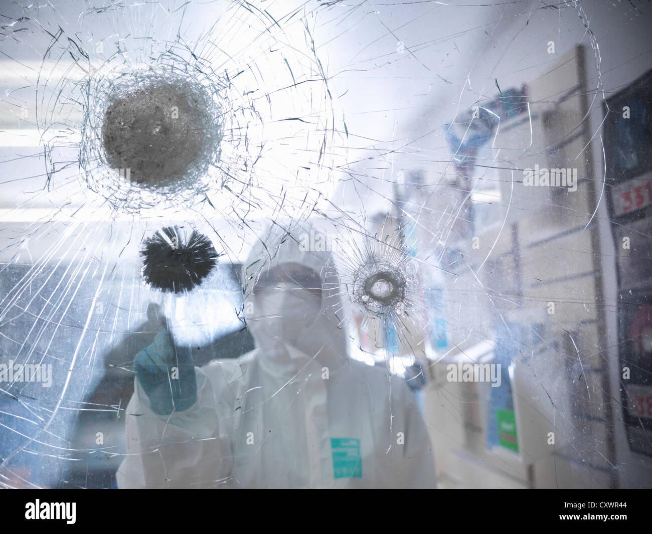 Forensische Wissenschaftler am zerbrochenen Fenster Stockbild