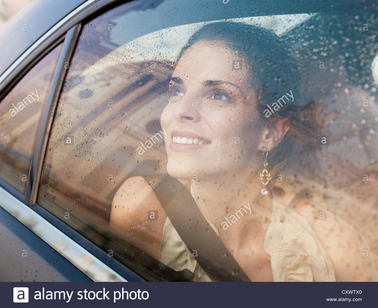 Lächelnde Frau suchen Autofenster Stockbild