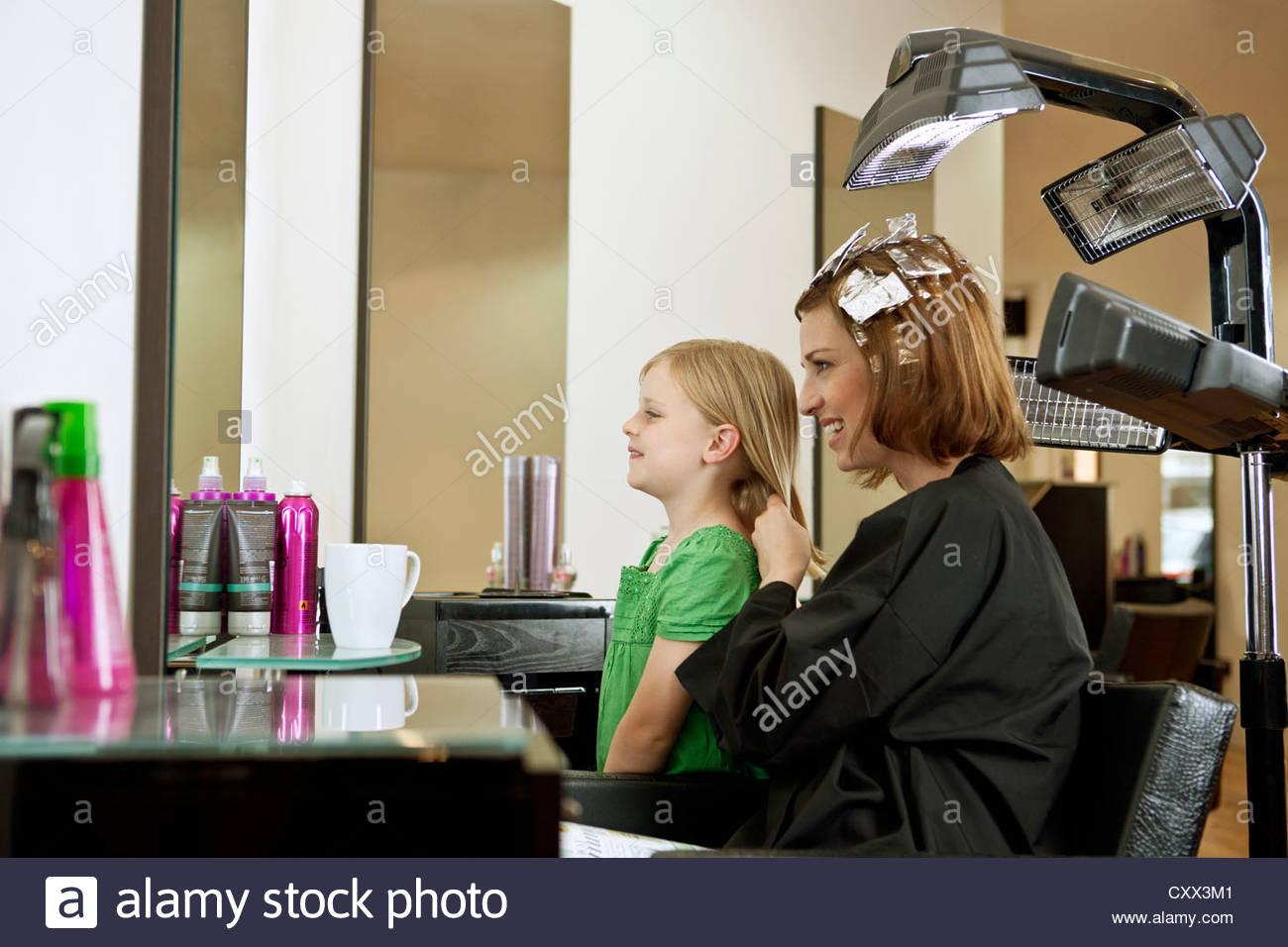 Mutter und Tochter in den Spiegel in einem Friseursalon Stockbild